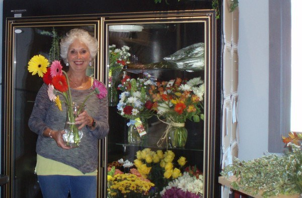 employee standing in front of a flower case holder a vase with flowers